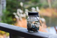 Rivers stones in mason jar with water. River stones in a mason jar filled with water sitting on the banister of a deck of a cottage Stock Photos