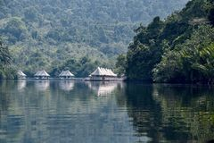 4 rivers tented jungle ecotourism hotel coming into view around a bend in the Kong River. Cambodia, Ko-Hong - March 2016: 4 rivers tented jungle ecotourism hotel royalty free stock image