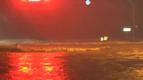 Rivers of water flowing down the city street, running traffic lights, after a tropical hurricane continue. Rivers of water flowing down the city street, running stock footage