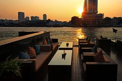 Riverside bar at sunset, Bangkok. Riverside bar near Chao phraya river with sunset scenics view in Bangkok, Thailand. Luxury outdoor restaurant with modern table Royalty Free Stock Photos