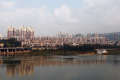 The riverside building. A vast red residential buildings built in the Jialing river, and the Cargo ships sailing on the river royalty free stock photography