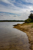 Riverside. Calm riverside beach with cloudy sky stock image