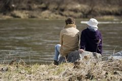 Riverside conversations. Couple sitting at a riverside engaged in conversation Royalty Free Stock Image