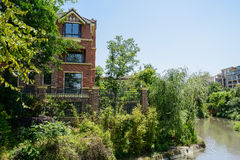 Riverside dwelling buildings in summer woods on sunny day Stock Photos