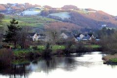 Hamlet, riverside, beneath green and frosty hillside Royalty Free Stock Photos