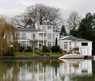 Riverside House. Winter scene of a Luxurious Residence and Boathouse on the banks of a River in England Stock Photo