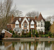 Riverside House. Winter scene of a Luxurious Residence  on the banks of a River in England Royalty Free Stock Image