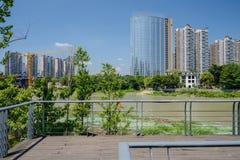 Riverside planked foot-bridge in modern city of sunny summer Stock Photo