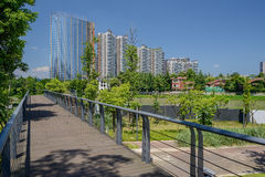 Riverside planked footbridge in modern city of sunny verdant sum Royalty Free Stock Photos