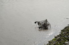 Riverside pollution. Metal supermarket shopping trolley thrown into the River Thames, London, England royalty free stock photo