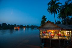 Riverside restaurant near Mekong River at twilight. Coconut trees silhouette, Beautiful lighting, restaurant and sunset sky. Backgrounds. Don Det, Don Khon stock photos