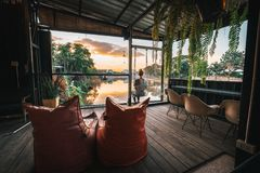 Riverside restaurant seats and tables near Chiang Mai during sunset in Lampang, Thailand. royalty free stock photo