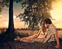 Riverside sunset kiss. Young couple kissing at riverside sunset Royalty Free Stock Photography