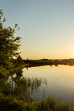 Riverside at sunset. Next to fields Royalty Free Stock Photos