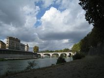 Riverside of Tevere with view on bridge and sky with white clouds. In the distance a house on the embankment Royalty Free Stock Photos