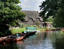 Riverside Thatched Cottage. With moored rowing boats in the foreground Stock Photo