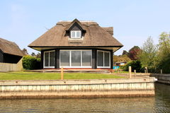 Riverside Thatched Cottage. An image of a riverside cottage with a thatched roof on the Norfolk Broads, England Royalty Free Stock Images