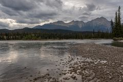 A riverside view down the river at sunset of the Athabasca River as it weaves its way through the Jasper National Park, Canada, on. A cloudy day, low clouds stock photo