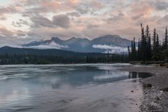 A riverside view at sunset of the Athabasca River as it weaves its way through the Jasper National Park, Canada, on a cloudy day. Low clouds hugging the stock photography