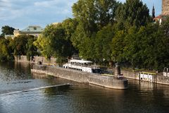 Riverside of Vltava River in Prague. Prague,  Czech Republic - August 19, 2017: Touristic boat in riverside of Vltava River in Prague at sunset against sky Royalty Free Stock Images