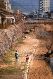 Riverside walk. Matsumoto, Japan - March 06, 2015: Woman and child walk alongside the Metoba River in Matsumoto Stock Image