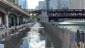Riverwalk in Chicago utilized by children playing in splash pad, commuters hurrying, runners, tourists, & elevated `el` train. Riverwalk in Chicago utilized by stock video footage