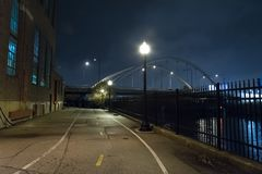 Riverwalk promenade and city bridge at night. Stock Images