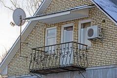 Rivesta di ferro il balcone con le finestre e una porta sul muro di mattoni della casa Fotografie Stock Libere da Diritti