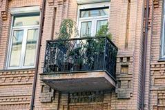Rivesta di ferro il balcone ed i vasi da fiori con le piante verdi con una finestra su una parete marrone Immagine Stock