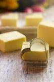 Rivesta di ferro il cuore sui precedenti della caramella gommosa e molle gialla Fotografie Stock