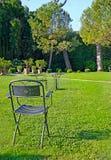 Rivesta di ferro la presidenza e la tabella in un bello giardino verde Fotografia Stock Libera da Diritti