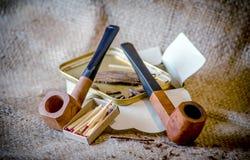 rivesta i tubi e un barattolo di pannelli del tabacco del fiocco con una scatola di bastoni della partita Fotografia Stock Libera da Diritti