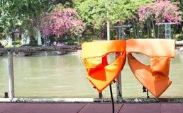 Rivestimenti arancio di sicurezza di vita secchi sul recinto Immagini Stock Libere da Diritti