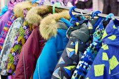 Rivestimenti di inverno dei bambini sul gancio in deposito Immagine Stock