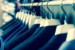 Rivestimenti sui ganci nel negozio di vestiti degli uomini Fotografia Stock Libera da Diritti