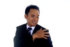 Rivestimento asiatico di pulizia dell'uomo d'affari con la mano isolata su un fondo bianco Immagine Stock