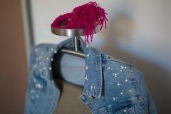Rivestimento dei jeans con le perle bianche ed i pantaloni beige che appendono su uno scaffale del cappotto del metallo fotografia stock libera da diritti