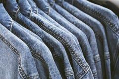 Rivestimento dei jeans di modo sui ganci Fotografie Stock Libere da Diritti