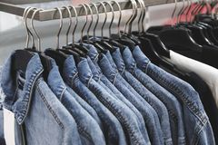 Rivestimento dei jeans di modo sui ganci Fotografie Stock