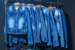 Rivestimento dei jeans di modo sui ganci Fotografia Stock Libera da Diritti