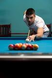 Rivestimento del giovane per colpire palla sul biliardo Fotografie Stock Libere da Diritti