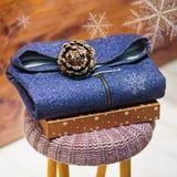 Rivestimento piegato del denim su una sedia tricottata e su un contenitore di regalo Fotografia Stock