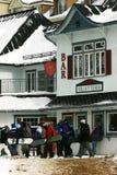 Rivestimento-in su degli Snowboarders per comprare i biglietti Immagine Stock