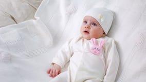 Rivestimento tricottato bianco della neonata con coniglio rosa stock footage