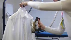 Rivestire di ferro del vapore della camicia dell'uomo bianco nel lavaggio a secco stock footage