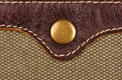Rivet button on the leather and fabric. Macro photo Stock Photos