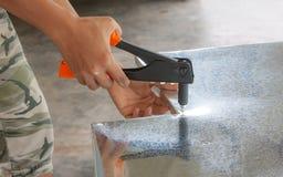 Rivet zinc sheet. Man use  equipment to rivet zinc sheet with frame Royalty Free Stock Photo