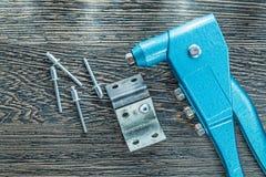 Rivetage des vis de rivets de pinces sur le conseil en bois photographie stock
