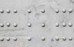 Riveted with button-head rivets metal plate detail of a bridge painted in gray Royalty Free Stock Image