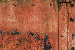Riveted Corroded Rusty Metal Plates With Cracked Peeled Off Flaky Red Anti-corrosive Paint And Patches Of Tar And Rust. Old, scrapped, badly corroded rusty river Royalty Free Stock Photography